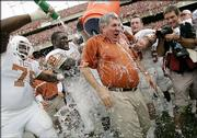 Texas coach Mack Brown gets dunked by William Winston (78), Brian Orakpo (98) and Brian Robison (39) during the closing seconds of the Longhorns' victory over Texas A&M. Texas won, 