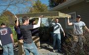 Pi Kappa Phi fraternity members at Kansas University help construct a house ramp for an elderly Lawrence resident earlier this month. Greek organization members say they do many public service activities, but their reputations are harmed by hazing and partying allegations.