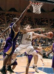 West Virginia guard Johannes Herber (5) goes up for an acrobatic shot as LSU's Glen Davis defends. The Tigers beat the No. 13-ranked Mountaineers, 71-68, Saturday in Morgantown, W.Va.