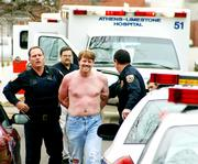 Farron Barksdale smiles as he is taken to a squad car in Athens, Ala., in this 2004 file photo after he allegedly gunned down two Athens police officers. People with a history of mental illness are banned by federal law from purchasing guns.