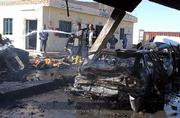 Iraqi firefighters spray water on burned cars after a suicide bomber killed 12 people Saturday when he drove his pickup into a crowded gasoline station in Samarra, Iraq.