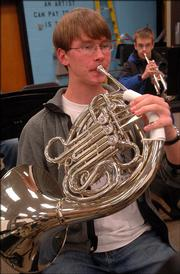 Lawrence High School juniors Sam Huneke, foreground left, on French horn and Evan Hunter, background right, on trumpet, rehearse in the LHS Symphonic Band. The band members are two of  several LHS and Free State High School musicians and singers who have been selected to Northeast Kansas district honor band and choir. Lawrence high schools place a disproportionately high number of students in the district honor band and choir.