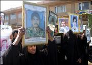 Iraqi women hold pictures of their relatives during a demonstration asking for the death penalty for ousted dictator Saddam Hussein on Sunday in Najaf, Iraq. According to relatives, people shown in the pictures were killed by Saddam Hussein's regime after the suppression of a Shiite uprising in the south of Iraq in 1991.