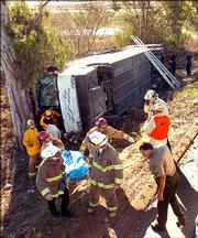 Rescue personnel remove one of two people killed when a Greyhound bus flipped over Sunday in Santa Maria, Calif. The bus was headed from Los Angeles to San Francisco when it rolled onto its side, killing two and injuring more than three dozen others.