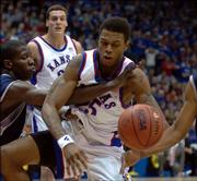 KU's Brandon Rush, right, fights for a loose ball with Kyle Shiloh as Sasha Kaun, back, looks on.