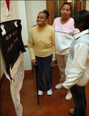 From left, Vivian Wilson, Carolyn Edwards and Tiffany Baker look at the quilt panel dedicated to Edwards' son, Nelson Bluitt, who died of AIDS in 1995. The panel was dedicated Thursday at a ceremony at Plymouth Congregational Church as part of World AIDS Day.