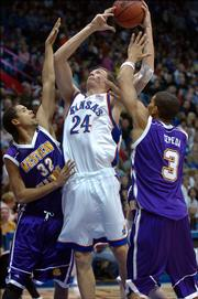 KU's Sasha Kaun takes a shot against Western Illinois' Chris Gonzalez, left, and Eliz Cepeda in the first half.