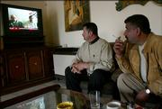 Two Iraqi men watch a TV news broadcast showing Westerners held captive as they sit inside a cafe in Basra, Iraq. The Iraqi group holding the hostages - two Canadians, a Briton and an American - have threatened to kill them if demands are not met by Dec. 8.