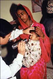 "A child receives an eye exam through ""A Solution in Sight,"" a program sponsored by Alternative Gifts International that provides eye exams, surgery and glasses to women and 