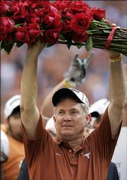 Texas coach Mack Brown holds a bundle of roses after beating Colorado, 70-3, to win the Big 12 title. The Longhorns clinched a berth in the Rose Bowl with the victory Saturday in Houston. Next up for UT? Top-ranked USC, which hammered UCLA, 66-19.