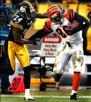 Pittsburgh Steelers cornerback Ike Taylor (24) hauls down Cinncinati's Tab Perry (88) after a 94-yard kickoff return in the third quarter. The return set up a Rudi Johnson touchdown. The Bengals beat the Steelers, 38-31, Sunday in Pittsburgh and established a two-game lead in the AFC North.