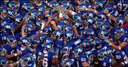 A sea of helmets converge at the center of Memorial Field as the Jayhawks huddle before kickoff against Florida Atlantic on Sept. 3. A report based on academic performance and graduation rates released Monday ranks the KU team 47 out of 56 teams selected for bowl games.