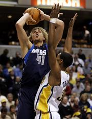 Dallas' Dirk Nowitzki, left, shoots over Indiana's Danny Granger. Nowitzki scored 31 points to lead the Mavericks past the Pacers, 84-75, Tuesday night in Indianapolis.
