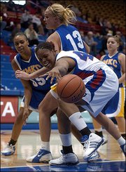 "Kansas University&squot;s Crystal Kemp, front, stretches for the ball while holding off UMKC&squot;s Alysa Klein (13) and Stephanie Brown in the Jayhawks&squot; 73-51 victory. Kemp led KU with 16 points Wednesday in Allen Fieldhouse.<br> <a href= ""http://www2.kusports.com/photos/galleries/2005/dec/08/ku_vs_umkc_120705/8930/"" target=""_new"" onclick= ""window.open(&squot;http://www2.kusports.com/photos/galleries/2005/dec/08/ku_vs_umkc_120705/8930/&squot;,&squot;Photo&squot;,&squot;height=650,width=625,screenX=10,screenY=10,&squot; + &squot;scrollbars,resizable&squot;); return false;""> <img src=""http://www.ljworld.com/art/icons/icon_photo.gif"" border= ""0"" alt=""photo""> Photo Gallery: KU vs. UMKC</a><br>"