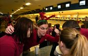 Target employee Kathy Bauman, center, gives a pep talk to fellow bowlers and employees Amy Lewis, left, Steph Barkmeyer and Justin Schiffner as their team competes against their Target co-workers during the company's Christmas party Tuesday afternoon at Royal Crest Lanes, 933 Iowa.