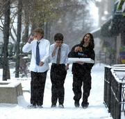 West Junior High freshmen from left, Daniel Aul, Kyle Andersen and Zach Ortiz make their way down Massachusetts Street eating pizza as the snow accumulated Wednesday. The snow is expected to drop off today, but temperatures will still be icy, with a high of 17 expected.