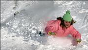Haley Blansit, 12, slides down a snow-covered hill in Overland Park. A winter storm passed through the area, closing schools Thursday and leaving as much as a foot of snow in northeast Kansas.