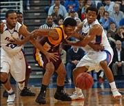 Bethune-Cookman's Brandon Edwards, center, tries to hold back Florida's Walter Hodge, left, and Taurean Green as they chase a loose ball during Friday's game in Gainesville, Fla. Florida won easily, 88-58.