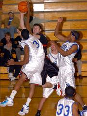 Sumner's Brian Johnson fouls Lawrence High's Tyler Knight.