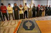 Ehab Lotayef, an envoy of the Canadian Islamic Congress, fifth from left, gives Friday Muslim prayers at the al-Imam al-Aadam mosque in a predominantly Sunni Arab neighborhood in Baghdad.