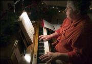 "Barbara Crumet plays ""O Holy Night"" during North Lawrence Christian Church&squot;s rehearsal of the Christmas pageant ""No Room For Jesus."" She had directed the pageant in years previous, but this year she opted to help with costumes and music instead."