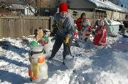 Donna Devosha, of Kansas City, Kan., shovels snow as Kristen Estrada, of Grain Valley, Mo.,   puts up a Santa Claus decoration.