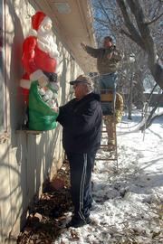 Maxine Lee's home will continue to be decorated for the holidays, even though she died last month. Lee's son, Tom Lee, left, and Dennis McBride joined a group of relatives putting up Christmas lights on Saturday. For 40 years, Maxine Lee lavishly decorated her house for the holidays.