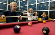 Reed Schenkel, 6, left, plays pool with Alyson Hertig, 8, Tuesday night at the East Lawrence Center, 1245 E. 15th St. A former mayor will introduce a proposal to county and city commissioners to build a new recreation center in Lawrence.
