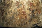 The National Geographic Society has released a photo showing a detail from a Mayan mural found at San Bartolo in Guatemala. The mural depicts the birth of the cosmos and the divine right of a king, and this portion shows the son of the maize god, patron of kings, with a pair of birds tied to his woven hunting basket, letting blood and offering a sacrificed turkey before one of five cosmic trees, according to the society.