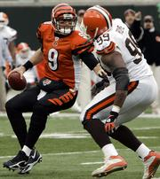 Cincinnati quarterback Carson Palmer, left, tries to avoid Cleveland's Orpheus Roye. The action took place Sunday in Cincinnati. Palmer had his worst outing of the season in a game that was played in cold and windy conditions.