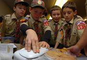 Webelo Scouts, from left, Matthew Hughes, 9, Austin Johanning, 10, Adam Hayes, 9, and Charlie Ghito, 9, vacuum-seal a homemade pie for a care package bound for U.S. soldiers in Iraq. The Webelos, along with Cub and Tiger Scouts of Troop 3013 made the holiday packages for soldiers at Camp Slayer in Iraq.