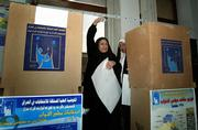 An Iraqi woman holds her ballot as she votes at an election center in Baghdad, Iraq. Iraqi voters faced tight security measures today as they cast ballots in a historic parliamentary election the U.S. hopes will build democracy and lay the groundwork for American troops to withdraw.