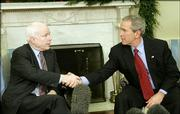 President Bush shakes hands Thursday with Sen. John McCain, R-Ariz., at the White House. The White House has agreed to ban cruel treatment of prisoners.