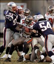 Tampa Bay's Carnell Williams (24) gets gang-tackled by New England's Richard Seymour (93), Rosevelt Colvin (59) and Tedy Bruschi (54) during the third quarter of the Patriots' 28-0 victory. New England won Saturday in Foxborough, Mass.