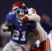 New York's Tiki Barber (21) escapes the grasp of Kansas City's Lional Dalton in the fourth quarter of the Giants' 27-17 victory. New York won Saturday in East Rutherford, N.J.