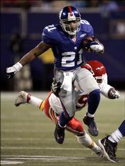 New York Giants running back Tiki bBarber (21) escapes the attempted tackle of Kansas City linebacker Kendrell Bell during the third quarter. Barber racked up 220 rushing yards, helping the Giants deliver the Chiefs another blow to their playoff hopes, 27-17, Saturday in East Rutherford, N.J.