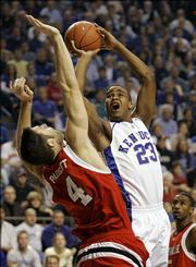 Louisville's David Padgett, left, defends Kentucky's Sheray Thomas. Padgett, a transfer from Kansas University, scored 12 points in the Cardinals' 73-61 loss Saturday in Lexington, Ky.