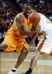 Tennessee's Stanley Asumnu, left, tries to maintain possession of the ball as Texas' Dion Dowell defends. Tennessee won, 95-78, Saturday in Austin, Texas.