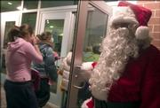 Santa holds open the door at the annual Bromelsick Christmas Party. The party was Saturday at the Lawrence Indoor Aquatic Center.