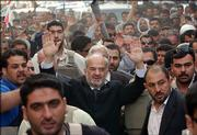 "Iraqi Prime Minister Ibrahim al-Jaafari waves to well-wishers Saturday in the Shiite holy city of Najaf, Iraq, where he made a nationally televised speech and congratulated Iraqis for their strong election turnout. He said the time has come for Iraqis of all religious affiliations to work together to ""build a new Iraq."""