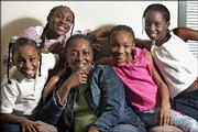 Mary McCray, center, sits Thursday in her apartment in Chicago with her granddaughters, from left, Wilshondra, 8, Rabriel, 12, Keoka, 9, and Mari, 10. Despite what they've been through, the girls are excited about Christmas in their new city.