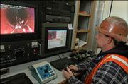I-CON employee Geoff Hanson, of Ottawa, checks sewer connections using a remote-controlled TV camera.