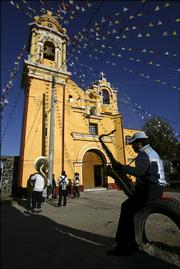 A band waits in front of the church of San Diego during a religious festival. Cholula has more religious festivals every year - about 400 - than any other town in Mexico.
