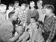 "Eager fans surround Wilt Chamberlain for an autograph in 1950s Lawrence. ""Wilt the Stilt"" led KU to the 1957 national championship game, losing in triple overtime to North Carolina, 54-53."