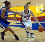 Kansas University guard Ivana Catic, right, drives around Creighton guard Brandy Bush. The Jayhawks beat the Bluejays, 63-52, Wednesday in Allen Fieldhouse.