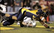 California's Anthony Felder, top, falls over Brigham Young quarterback John Beck in the second quarter of the Pioneer Purevision Las Vegas Bowl. Cal won, 35-28, Thursday in Vegas.