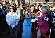 "Actress Q&squot;Orianka Kilcher, center, who plays Pocahontas in the movie, ""The New World,"" signs an autograph before the East Coast debut of the film Wednesday in Williamsburg, Va."