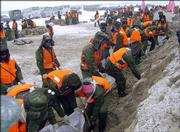 Chinese army soldiers fill sandbags near the town of Fuyuan on the Amur River at the Chinese-Russian border. Remnants from a toxic Benzene spill reached the Russian city of Khabarovsk on Thursday as a second toxic spill from a Chinese factory, this time involving cadmium, was reported.