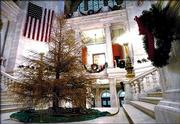 An 18-foot Colorado Blue Spruce Christmas tree stands brown and stripped of its needles Wednesday in the Rotunda of the Rhode Island Statehouse in Providence.
