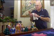 Dan Abrahamson dusts off some of the Nativities he made while he was in the Army in 1960.